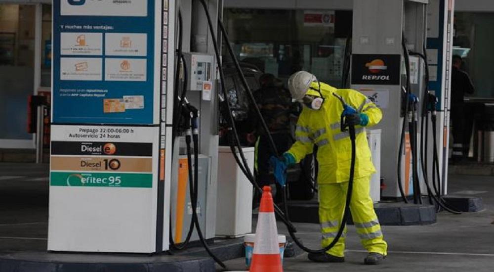 Trabajador de gasolinera convencional en tareas de desinfección.